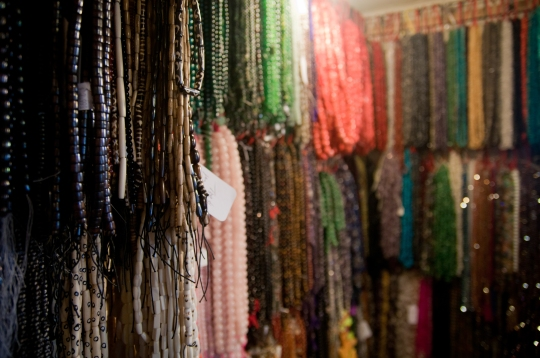Stringed beads made from crystal, wood, and other assorted stones hang on a wall in Things Lucky on Page and Ashbury Street